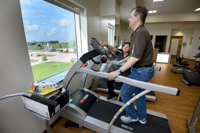 Hernandez increases the incline on a treadmill for a patient who is undergoing rehab for a condition that causes lower back and leg pain.