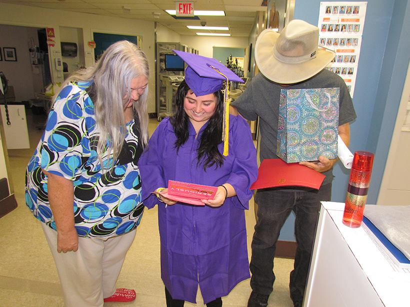 Deluna and her grandparents read a card from UTMB staff.