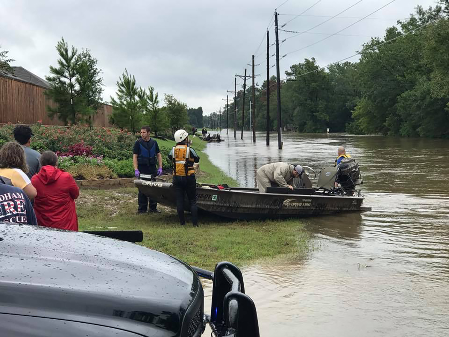 Cain bends over in his boat to unload supplies in between water rescues in The Woodlands area.