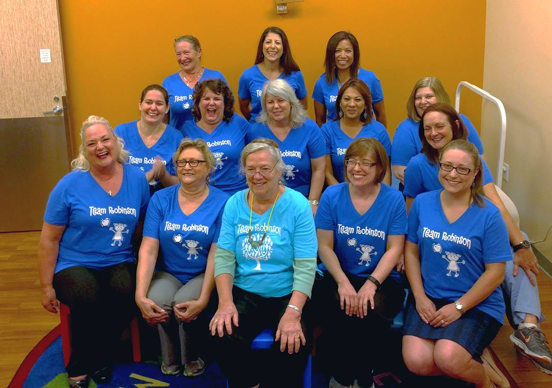 "Dr. Sally Robinson (first row, center) and her colleagues wearing ""Team Robinson"" shirts."