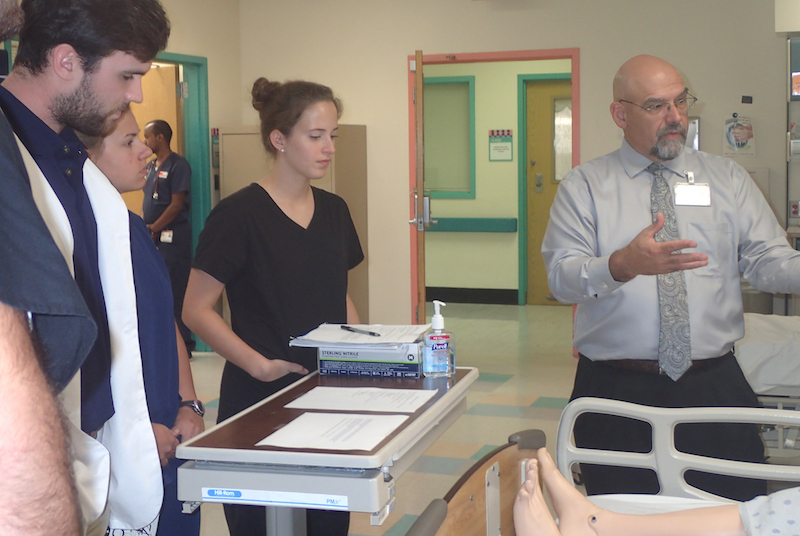 Dr. José Rojas works with students during a simulation.