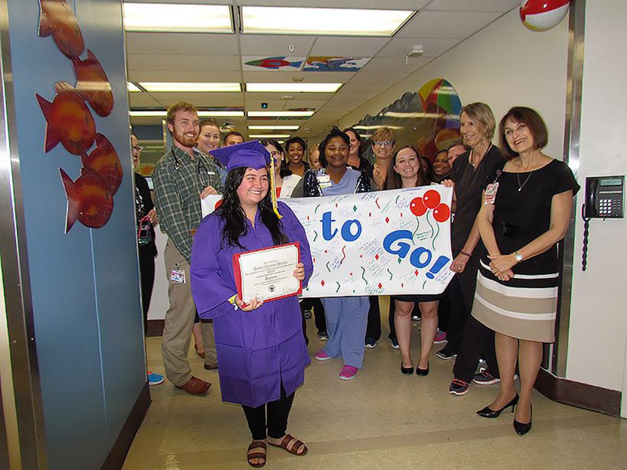 Taylor Deluna holds her diploma after being surprised by UTMB Children's Hospital staff.