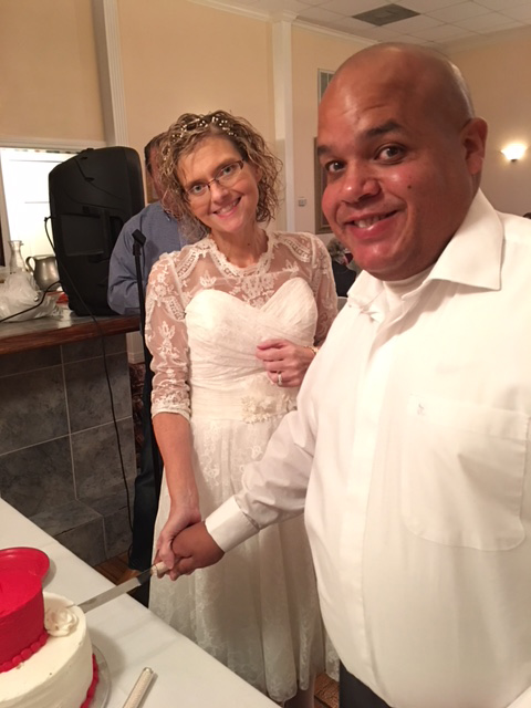 Amanda and Keith Johnson smile for a photo as they cut into their vow renewal cake.