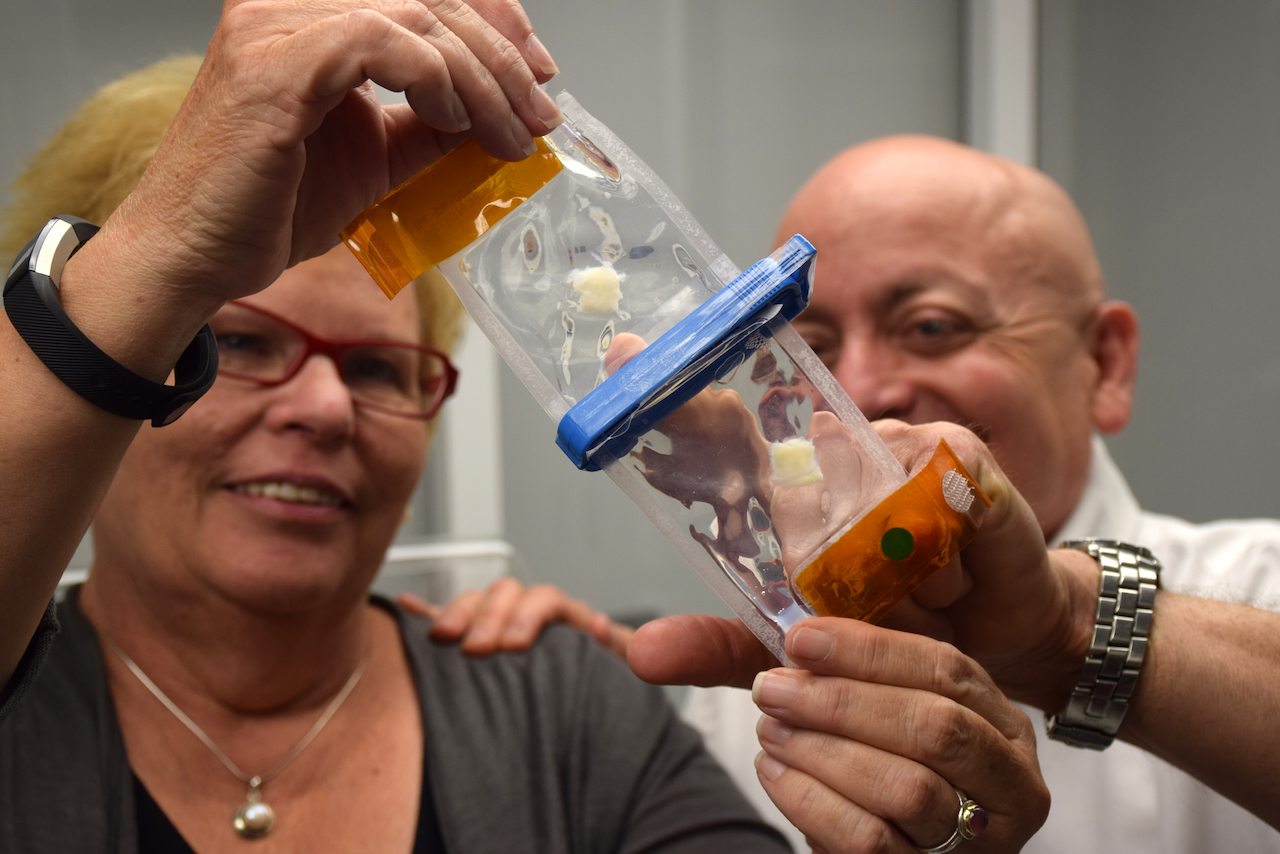 Dr. Joan Nichols and Dr. Joaquin Cortiella look at an example of a bioreactor pouch that contains lung progenitor and stem cells and pieces of lung scaffolding, similar to those sent to space in August.