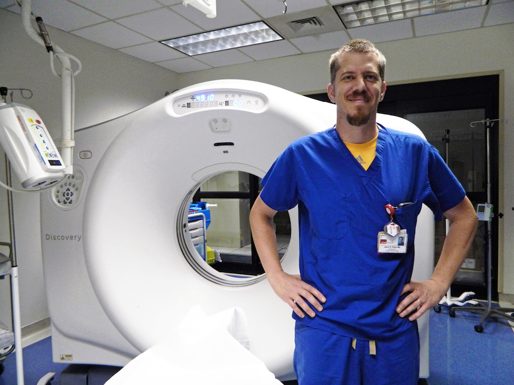 Dr. Jason Ross, a senior radiology resident, stands in front of a CT machine.