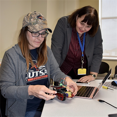 Dr. Marguerite Sognier (right) provides encouragement as teacher Kacey Sommers works on programming a robot.