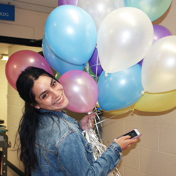 Student hold colorful balloons