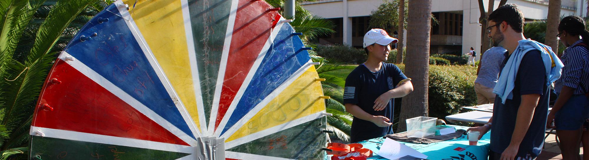 A student shows off a lizard a the Plazapalooza organization carnival