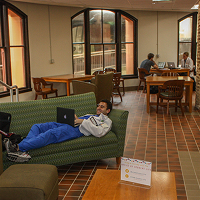Student laying on couch in study room with laptop