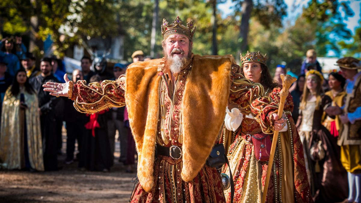 A man in a kingly, renaissance costume stands open armed addressing a crowd of costumed people.