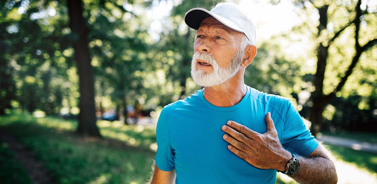 Older man holding chest