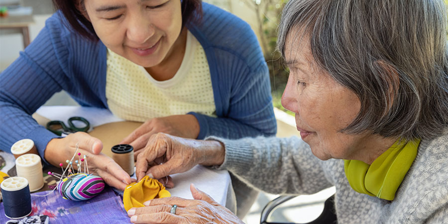 daughter helping elderly mother with sewing